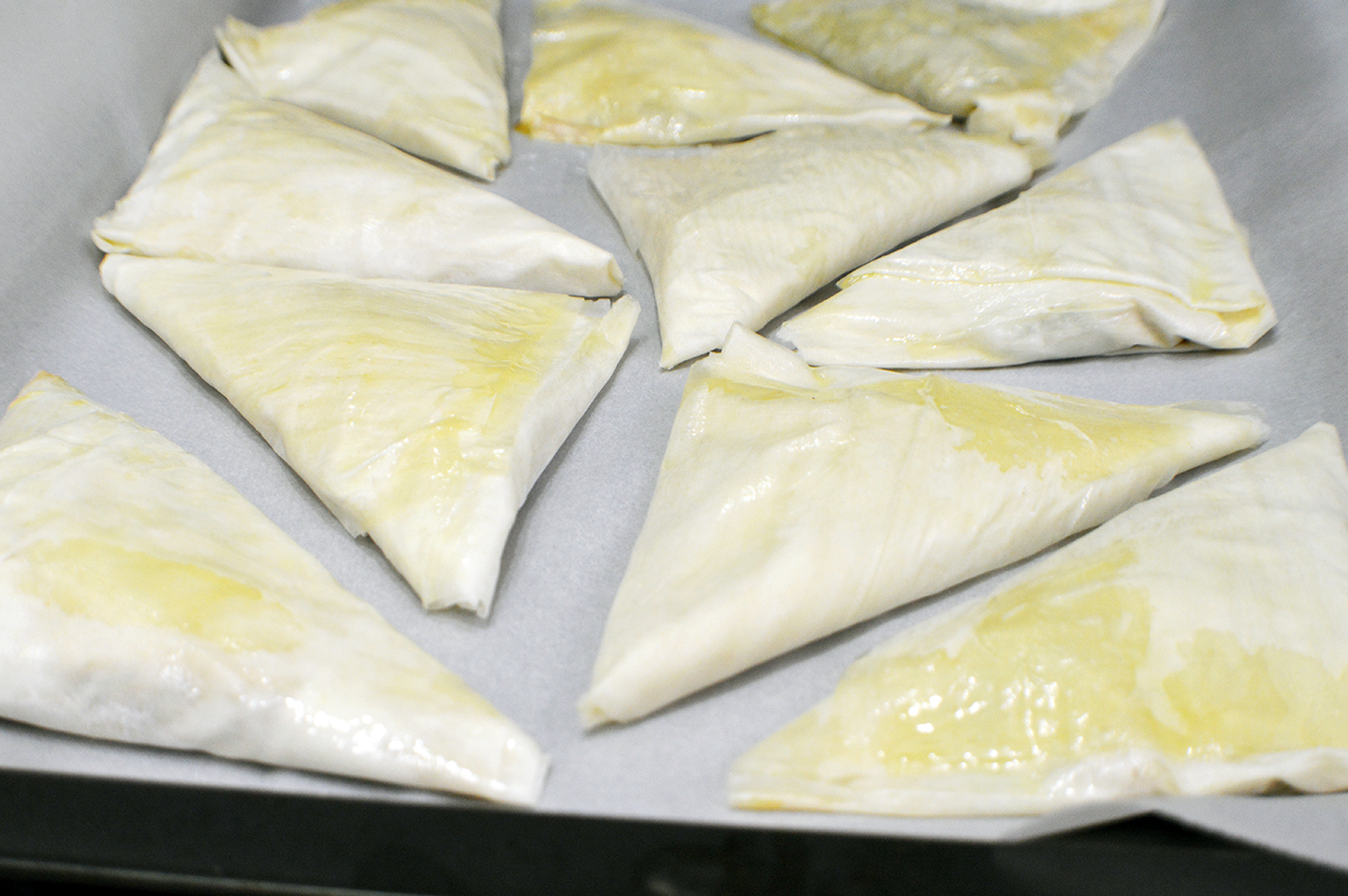 Arrange the spanakopita triangles on a baking sheet, then cook until ...